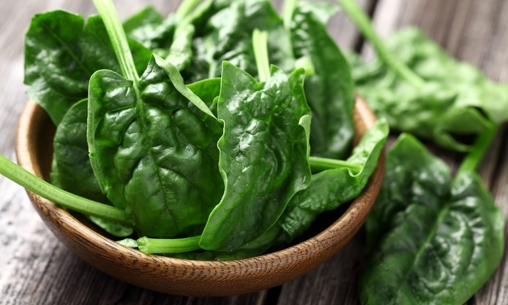 Raw spinach in brown bowl